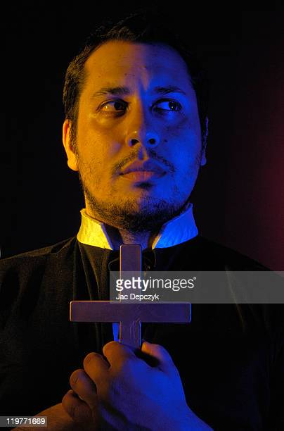young man holding crucifix, gold and blue light. - depczyk stock pictures, royalty-free photos & images