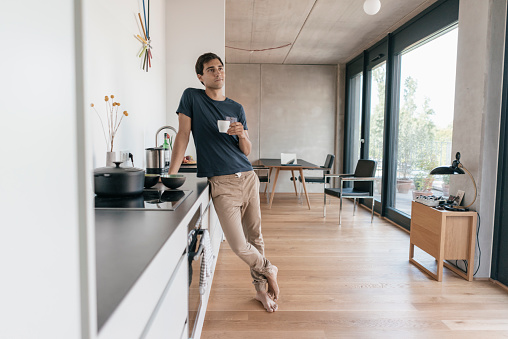 Young man holding cup of coffee in kitchen at home - gettyimageskorea
