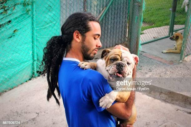 young man holding dog - rescue stock pictures, royalty-free photos & images