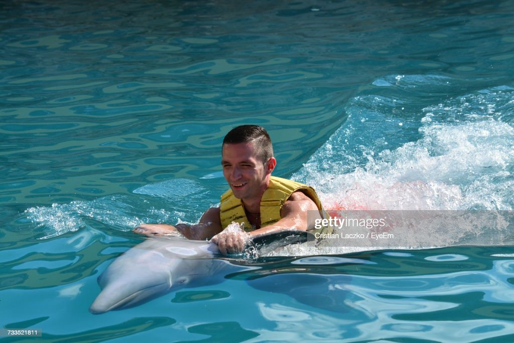 Young Man Holding Dolphin In Sea : Stock Photo