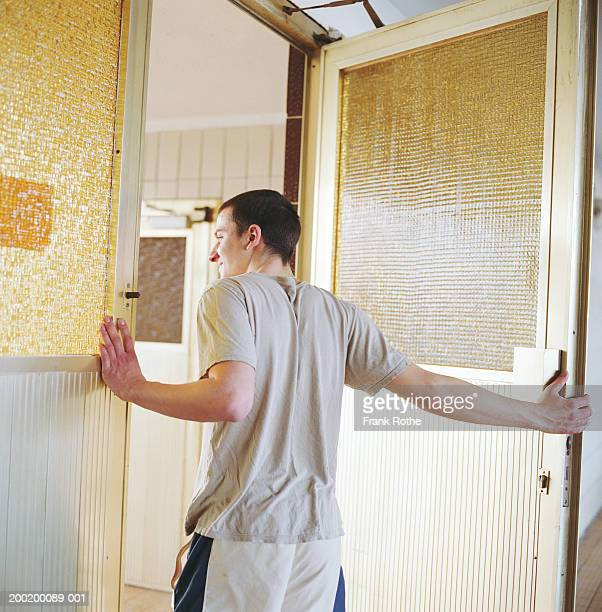 Young man holding door open, peering out, rear view
