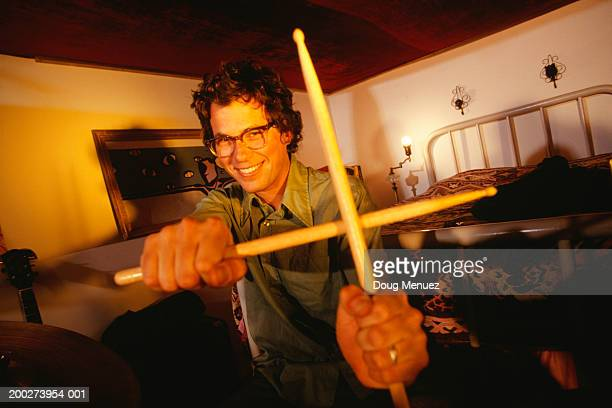Young man holding drumsticks crossed, portrait