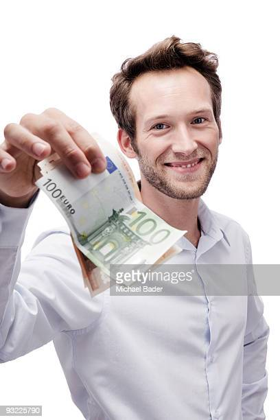 Young man holding Euro banknotes, smiling, portrait