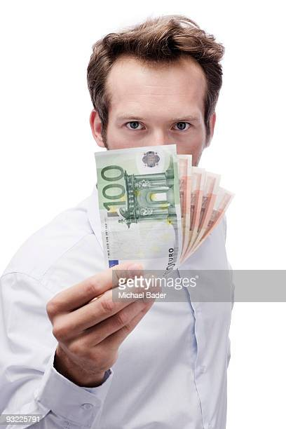 Young man holding Euro banknotes, portrait, close-up