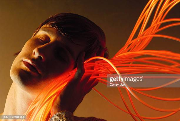 Young man holding fibre optic cables against cheek, eyes closed