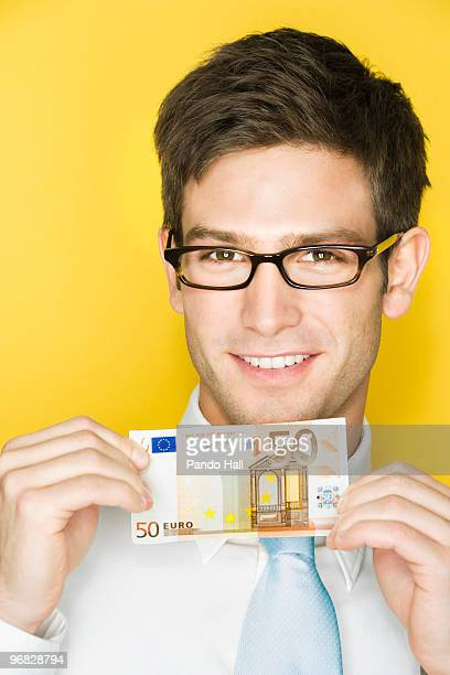 Young man holding fifty euro banknote, smiling