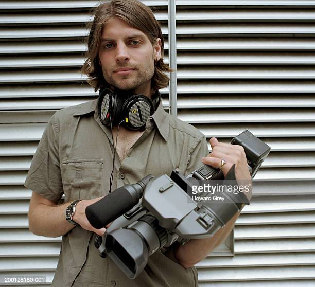 Young man holding film camera, portrait