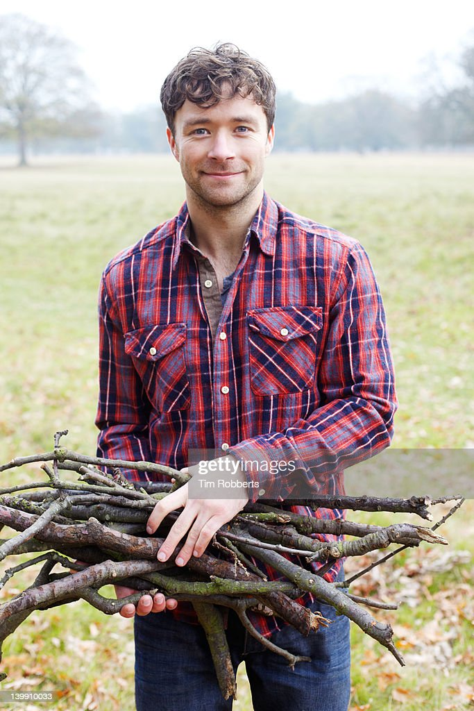 Young man holding firewood. : Stock Photo