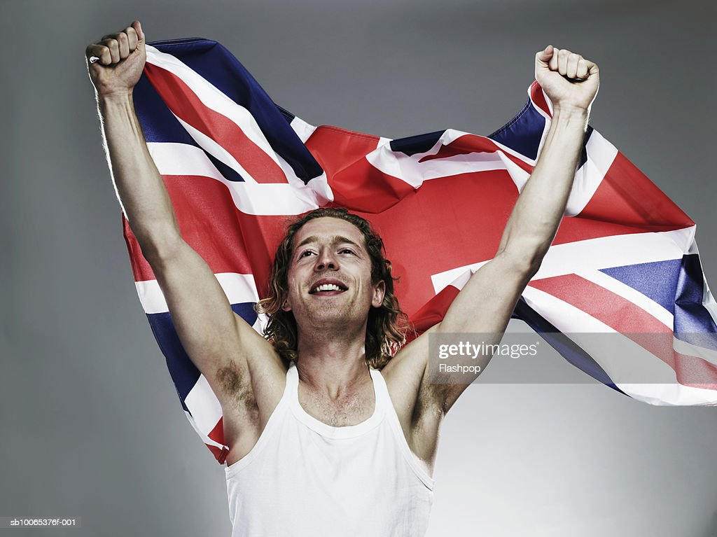 Young man holding flag, smiling, close-up : Foto stock