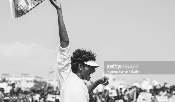 young man holding flag while shouting at rally with crowd in background - india politics stock pictures, royalty-free photos & images