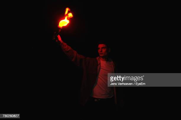 Young Man Holding Flaming Torch While Standing At Night