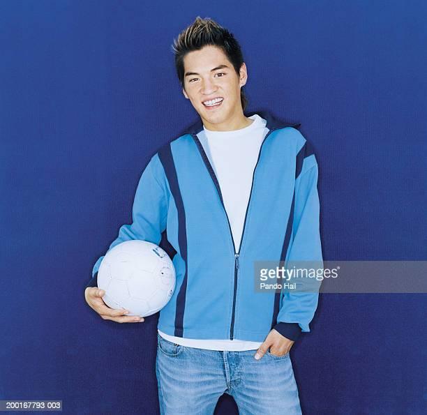 young man holding football, smiling, portrait - trainingsoberteil stock-fotos und bilder