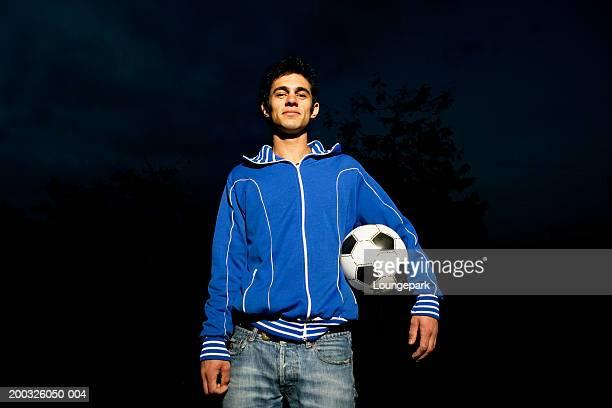 young man holding football under arm, smiling, portrait - trainingsoberteil stock-fotos und bilder