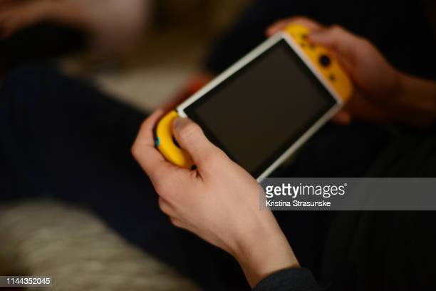 young man holding game console - kristina strasunske stock photos and pictures