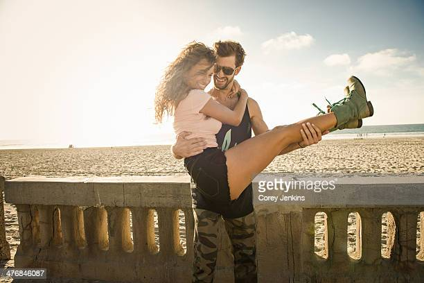 Young man holding girlfriend in arms at San Diego beach