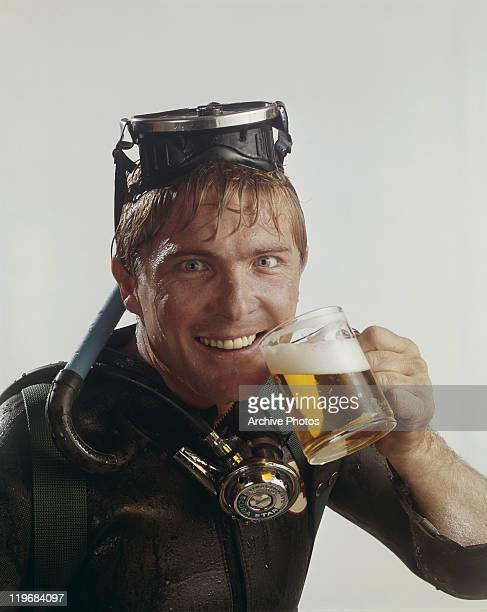 Young man holding glass of beer, portrait