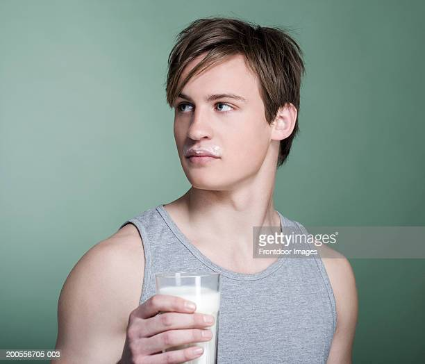 Young man holding glass of milk, close-up