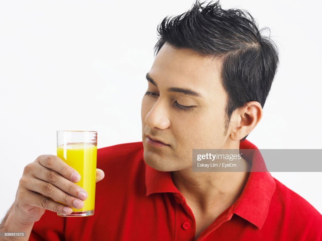 young man holding glass with orange juice against white background picture id938931570