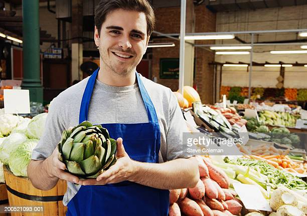 Young man holding globe artichoke at market stall, smiling, portrait