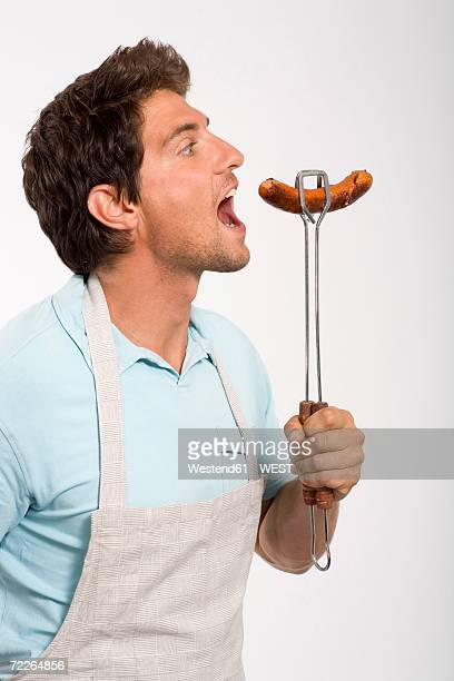 Young man holding grilled sausage, close up