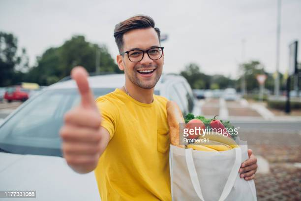 young man holding groceries in reusable bag and showing thumb up - carrying stock pictures, royalty-free photos & images