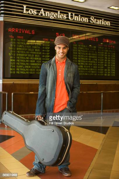 young man holding guitar case - union station los angeles stock photos and pictures
