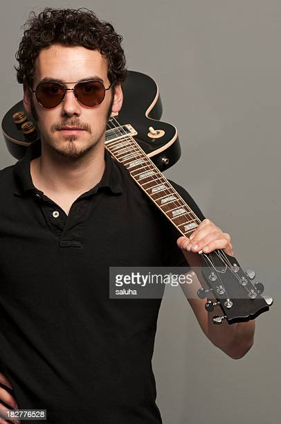 Young man holding guitar over shoulder wearing sunglasses