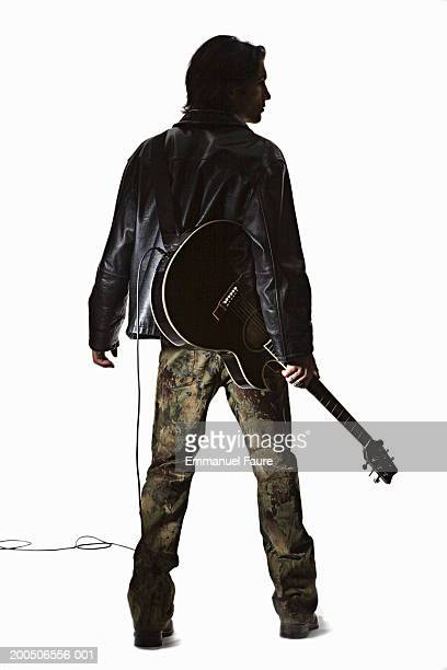 young man holding guitar, rear view - ギタリスト ストックフォトと画像