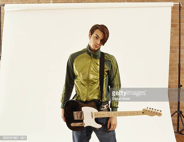 Young man holding guitar, standing in front of white screen, portrait