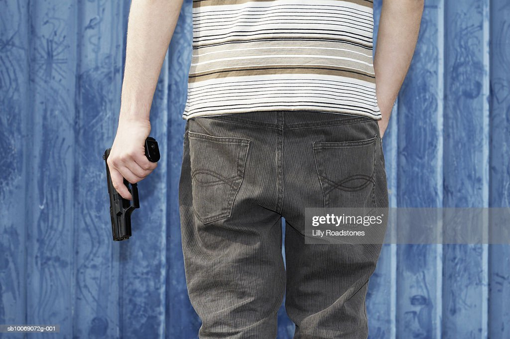 Young man holding gun, close-up, mid section : Stockfoto