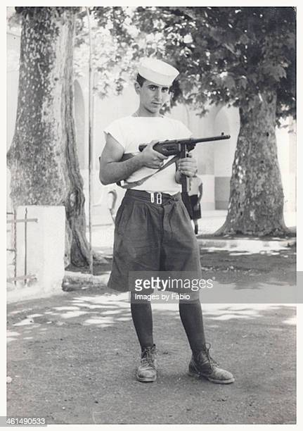 Young man holding gun during military service