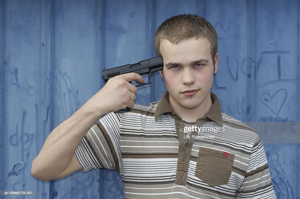 Young man holding gun to head, close-up, portrait : Stockfoto