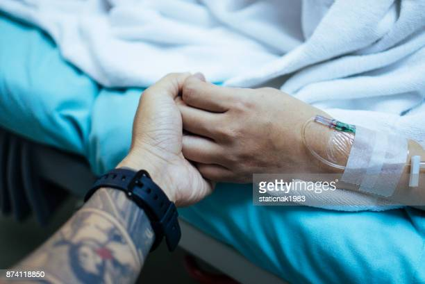 Young man holding hand of asian pregnant woman waiting in hospital bed