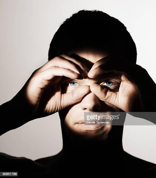 young man holding hands like binoculars