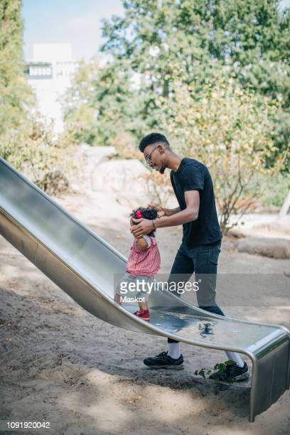 young man holding hands of daughter walking on slide at playground - stay at home father stock pictures, royalty-free photos & images