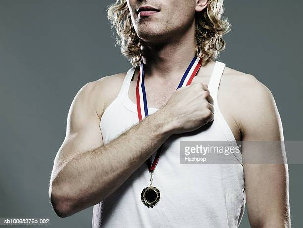 young man holding hands to heart, close-up, mid section - medalhista - fotografias e filmes do acervo