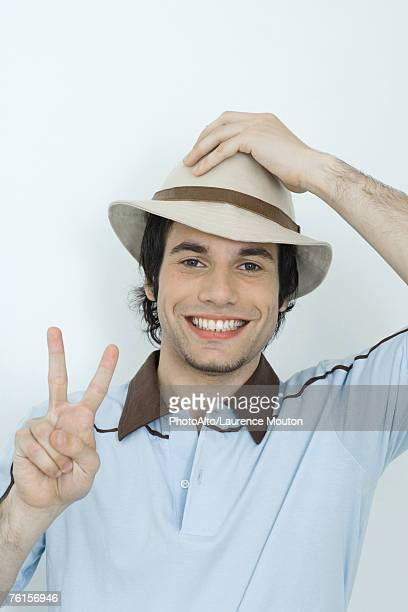 'Young man holding hat on head, holding up fingers in peace sign'