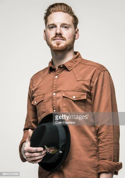 young man holding hat - brown hat stock photos and pictures