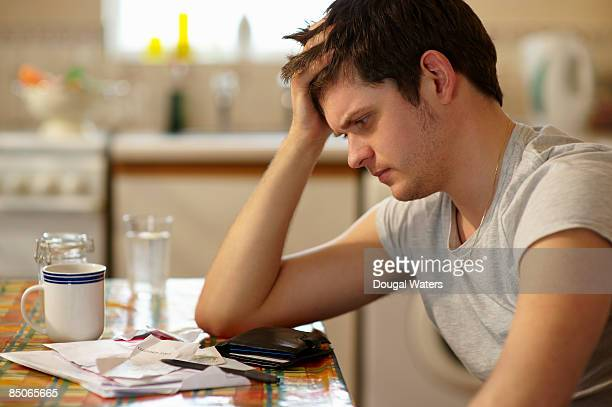 young man holding head looking at receipts. - worried stock pictures, royalty-free photos & images