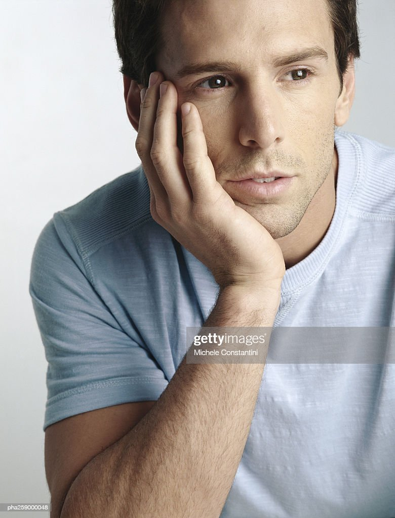 Young man holding head with hand, looking away, close-up : Stockfoto