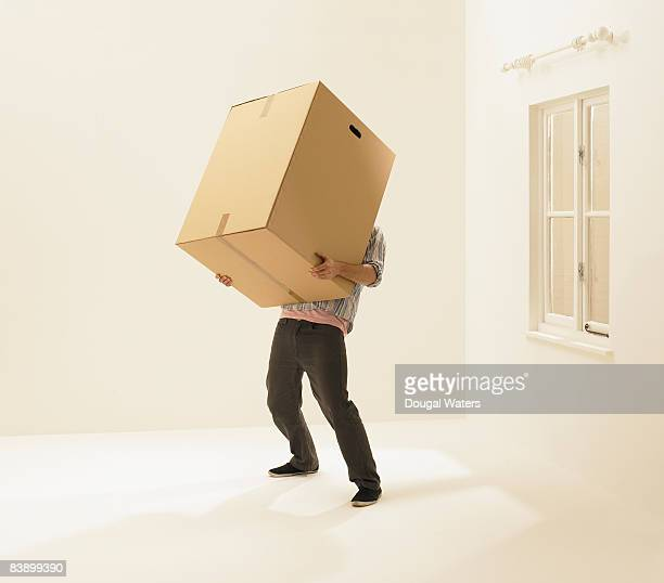 Young man holding heavy box.