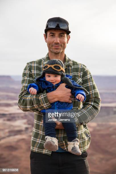 A young man holding his 4 month old baby.