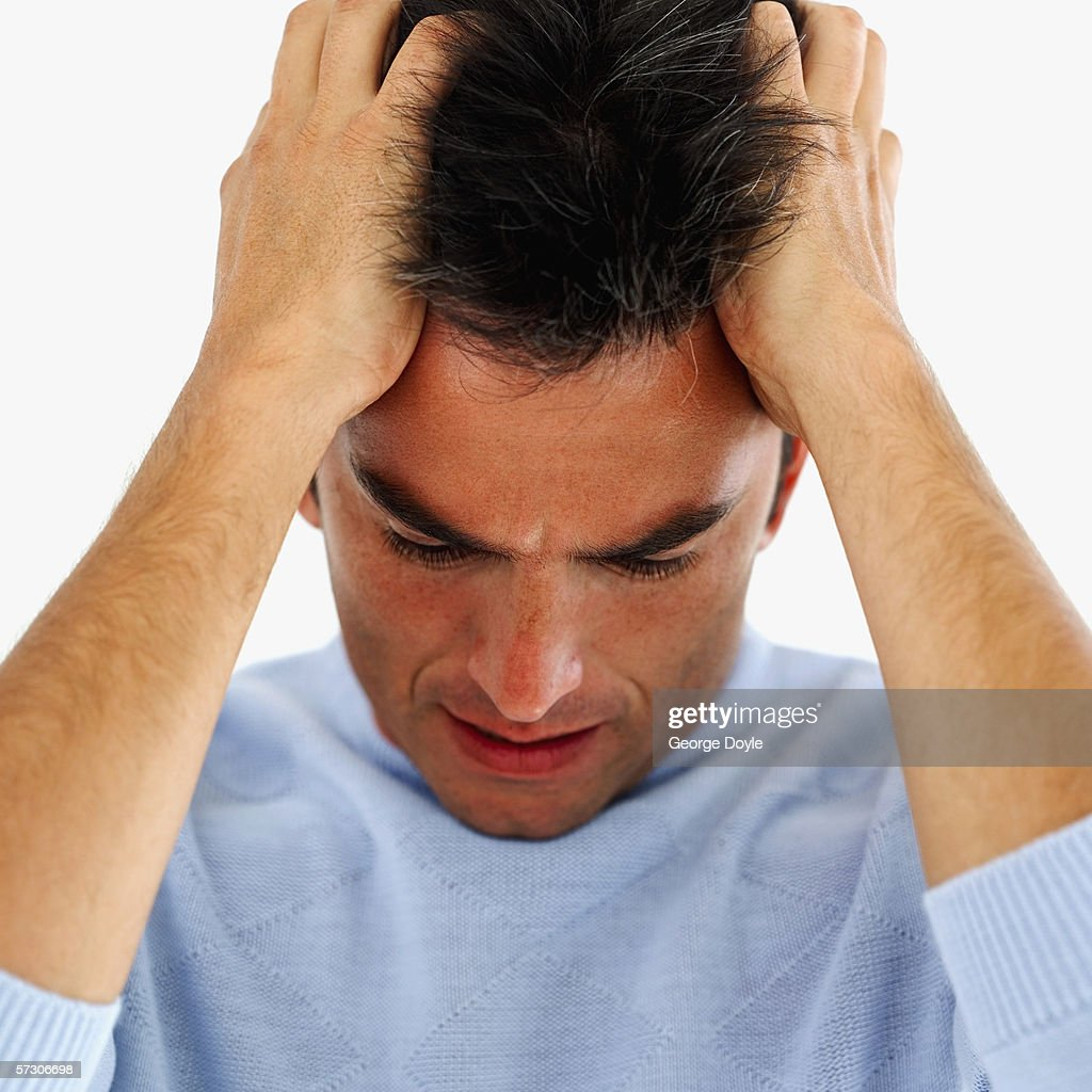Young man holding his hair in frustration : Stock Photo