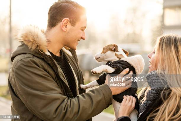 Young man holding his Jack Russell puppy towards the Sun