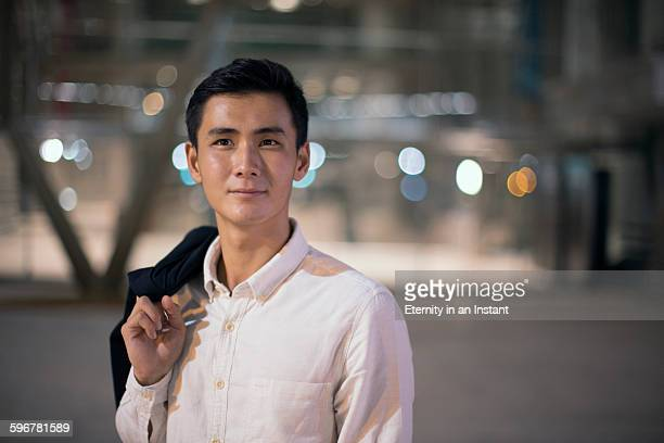 young man holding his jacket over his shoulder. - handsome chinese men stock pictures, royalty-free photos & images