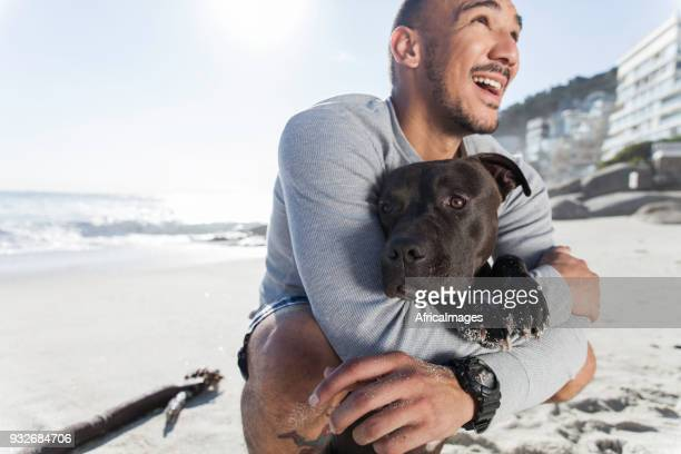 Young man holding his pit bull at the beach.