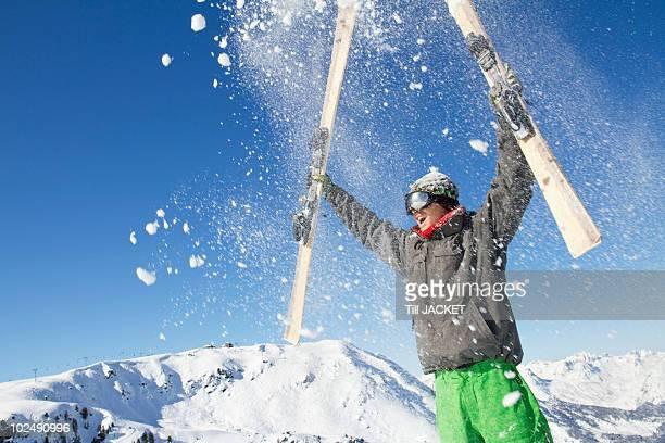 young man holding his skis above his head - trois vallees - fotografias e filmes do acervo