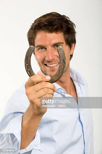 young man holding horseshoe, symbol for luck - hufeisen stock-fotos und bilder