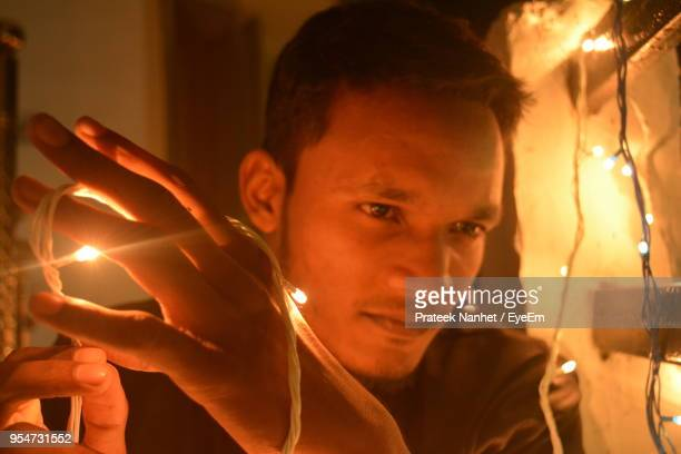 young man holding illuminated string light at home - indore stock photos and pictures