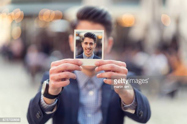 Young man holding instant photo in front of his face